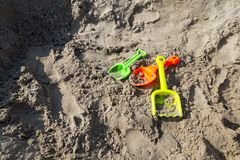 Green, orange, yellow plastic toy shovels on the beach sand or sand box stock images