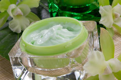 Green Orchids and Moisturising Cream. Closeup gorgeous blooming green colored Cattleyas orchid flowers and jars of cosmetics cream Royalty Free Stock Photo