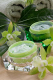 Green Orchids and Moisturising Cream. Closeup gorgeous blooming green colored Cattleyas orchid flowers and jars of cosmetics cream Royalty Free Stock Photography