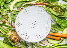 Green organic garden vegetables around  empty white colander, top view Royalty Free Stock Images
