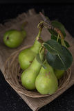 Green organic pears in basket on cloth closeup background Stock Photo