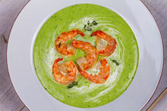 Green organic vegetable and creamy soup with shrimps. Royalty Free Stock Photo