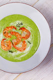 Green organic vegetable and creamy soup with shrimps. Stock Photo