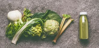 Green organic vegetables smoothie with chard, fennel, artichokes and rhubarb in bottle on gray granite table , top view. stock photo