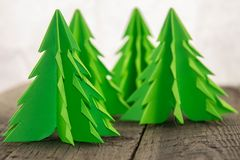 Green origami Christmas trees. On a rustic wooden surface and a white background Royalty Free Stock Photos