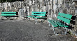 Green Outdoor Benches during a Sunny Day in Switzerland. Green benches made of wood and concrete photographed on a sunny spring day in Nyon, Switzerland. In this stock images