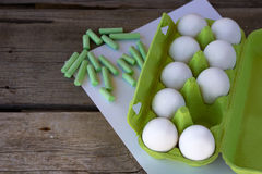 Green packing raw eggs and crayons Royalty Free Stock Image