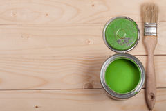 Green paint in the bank to repair and brush on the light wooden background with copy space for your text. Top view Royalty Free Stock Photography