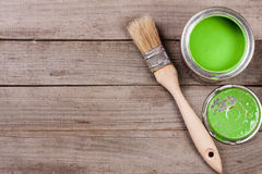 Green paint in the bank to repair and brush on the old wooden background with copy space for your text. Top view. Green paint in the bank to repair and paint Stock Images