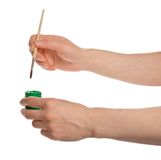Green paint and brush in the hands Stock Photo
