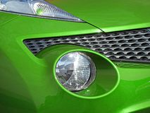 Green paint modern car vehicle lights headlamp cluster grille front detail. Photo of modern car detail to front showing headlamp headlight clusters and grille stock photos