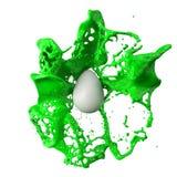 Green paint splash over a white easter egg. 3d illustration. Green paint splash over a white easter egg. suitable for easter, paint, and hobby themes. 3d stock illustration