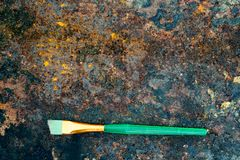 Green paintbrush on rusty table Royalty Free Stock Photos