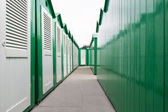 Green painted beach cabins with white doors. View down a row of green painted wooden beach cabins with white doors stock photography