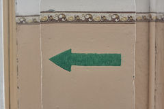 Green painted indicator, sign on old wall close up Stock Images