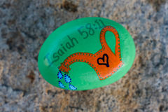 Green painted rock with orange watering can and Bible verse. Green painted shiny rock with picture of orange watering can and blue water drops coming from spout Stock Image
