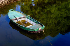 Green painted rowboat with a shallow layer of water Stock Photography