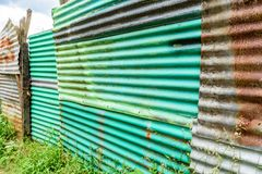 Green painted rusty corrugated iron fence royalty free stock photo