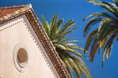 Green palms, blue sky, red roof. Red roof of a house and palm trees on blue sky background. May be used as a background for quotes and cover image Royalty Free Stock Photos