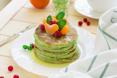 Green pancakes with spinach and bananas decorated citrus, mint and cranberry Stock Photography