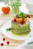 Green pancakes with spinach and bananas decorated citrus, mint and cranberry Royalty Free Stock Images