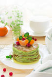 Green pancakes with spinach and bananas decorated citrus, mint and cranberry Royalty Free Stock Photos