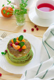 Green pancakes with spinach and bananas decorated citrus, mint and cranberry Stock Photos