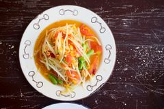 Green papaya salad. Or Som Tum Thai in white dish on wooden table Stock Images