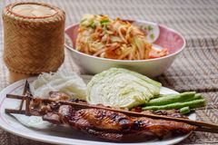 Green papaya salad with grilled chicken. On original thailand mat stock images