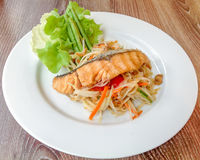 Green papaya salad with Salmon Grill. Green papaya salad is a spicy salad made from shredded unripe papaya. It is of Lao origin but it is also eaten throughout Royalty Free Stock Photography