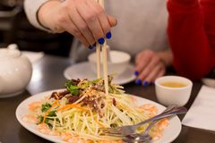 Green papaya salad with a woman`s hand holding chopsticks. royalty free stock images