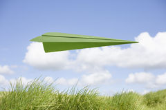 Green Paper Airplane. In flight over grass and with blue sky and fluffy clouds in the background Royalty Free Stock Images