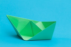 Green paper boat on blue background Royalty Free Stock Photography