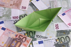 Green paper boat on Euro banknotes Royalty Free Stock Photo