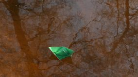 Green paper boat is floating on the water. Green paper boat is floating on water stock footage