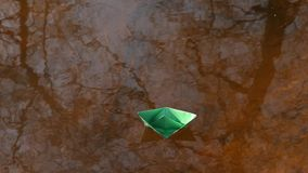 Green paper boat is floating on the water. Green paper boat is floating on water stock video