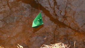 Green paper boat is floating on the water. Little green paper boat is floating on the water stock video