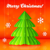 Green paper Christmas tree on orange background Stock Image