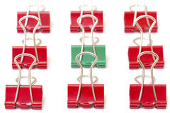 Green paper clip among red Royalty Free Stock Photography