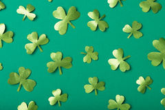 Green paper clovers. Paper clovers scattered over green background, top view Stock Photos