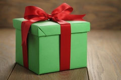 Green paper gift box gift box with lid and red ribbon bow on wood table with copy space. Shallow focus Stock Photography