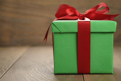 Green paper gift box gift box with lid and red ribbon bow on wood table with copy space. Shallow focus Royalty Free Stock Images