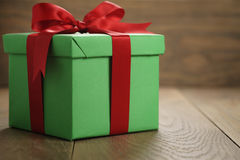 Green paper gift box gift box with lid and red ribbon bow on wood table with copy space. Shallow focus Stock Images