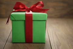 Green paper gift box gift box with lid and red ribbon bow on wood table with copy space. Shallow focus Stock Image