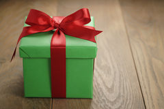 Green paper gift box gift box with lid and red ribbon bow on wood table with copy space. Shallow focus Royalty Free Stock Photography