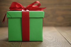 Green paper gift box gift box with lid and red ribbon bow on wood table with copy space. Shallow focus Stock Photos