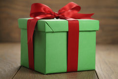 Green paper gift box gift box with lid and red ribbon bow on wood table. Shallow focus Stock Photos