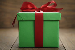 Green paper gift box gift box with lid and red ribbon bow on wood table. Shallow focus Royalty Free Stock Image