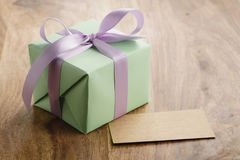 Green paper gift box with purple ribbon bow and empty greeting card on old wood table Stock Photos