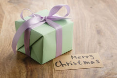 Green paper gift box with purple ribbon bow and merry christmas greeting card on old wood table Stock Photography
